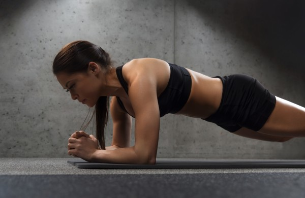 15545443-woman-doing-plank-exercise-on-mat-in-gym-600x390