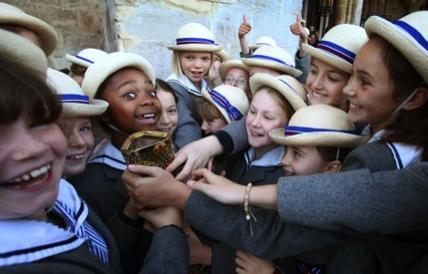 Schoolgirls from Leadenhall School, Salisbury, hold the Olympic Torch of Olympic gold medalist former sprinter Torchbearer 001 Michael Johnson at Salisbury Cathedral during Day 55 of the London 2012 Olympic Torch Relay.