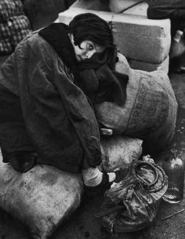 Little girl resting during the evacuation of the city, Barcelona, 1939