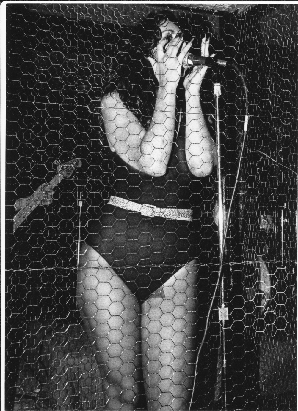 """Lucy Lamode of Killer Pussy inside chicken wire cage at Mad Garden, 1981. By Neal """"Doc"""" Holliday"""