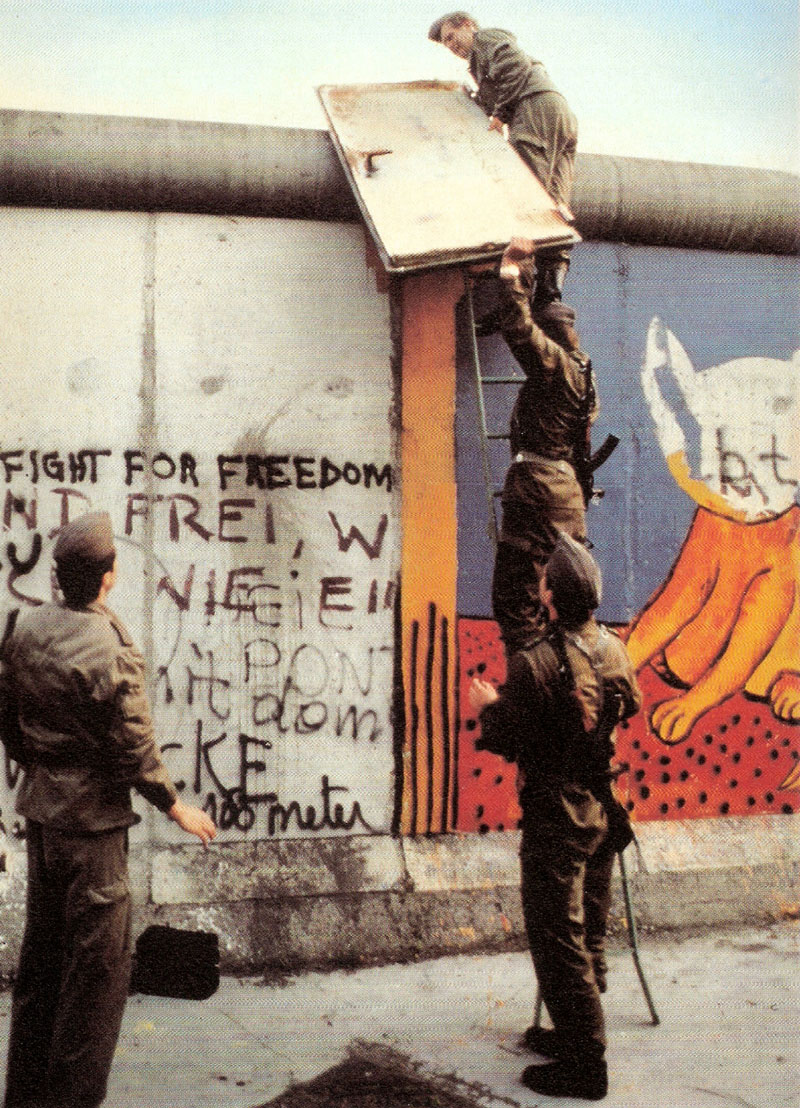 GDR soldiers removing a heavy iron door from the Berlin Wall and taking back to East Berlin after Noir had stuck it to the Wall.