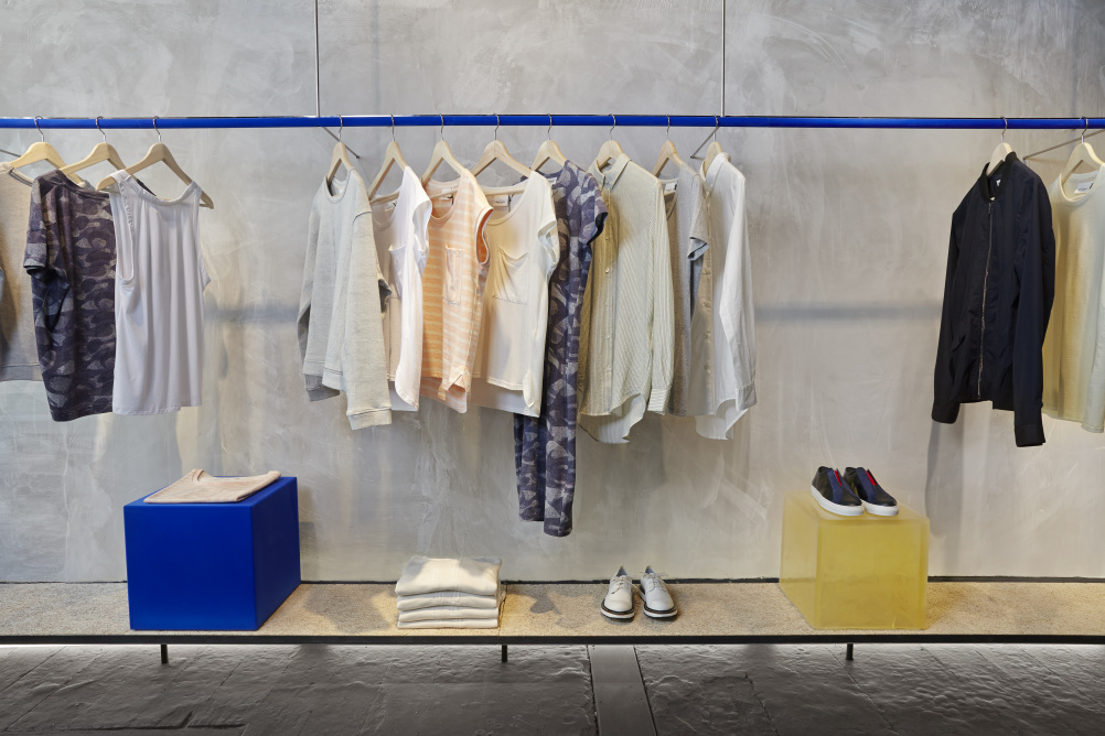 A blue clothing rail and raw concrete wall