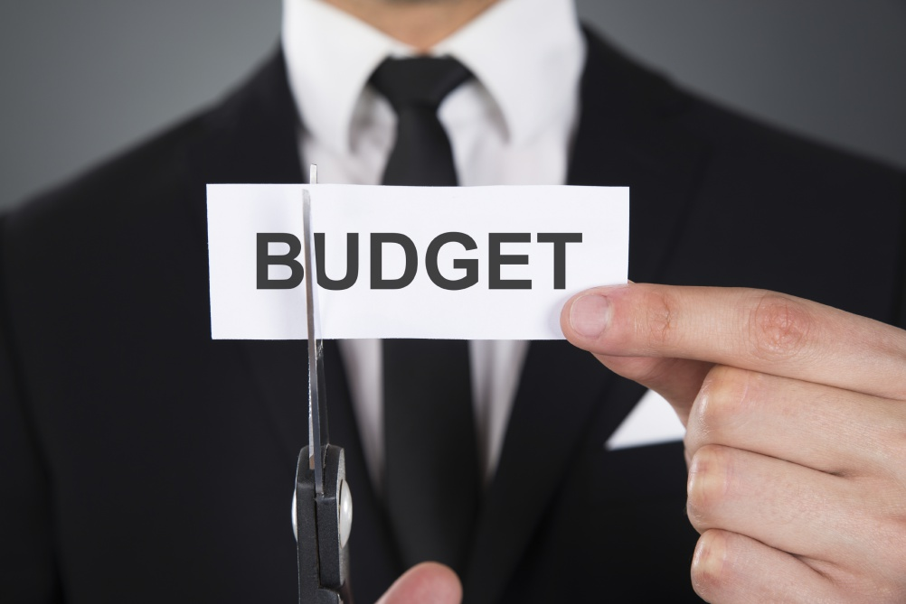 Businessman Cutting The Word Budget On Paper With Scissors