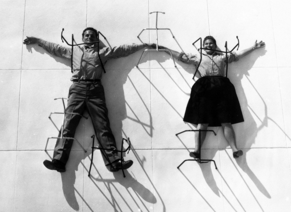 3. The World of Charles and Ray Eames. Charles and Ray Eames posing with chair bases © Eames Office LLC