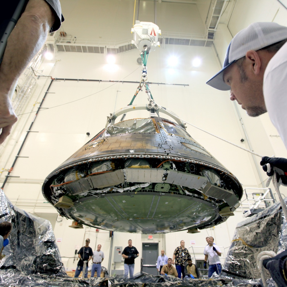 Workers preparing the Orion spacecraft that flew on Exploration Flight Test-1 in 2014 for transport