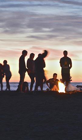 Fiesta en la playa con hoguera por la noche
