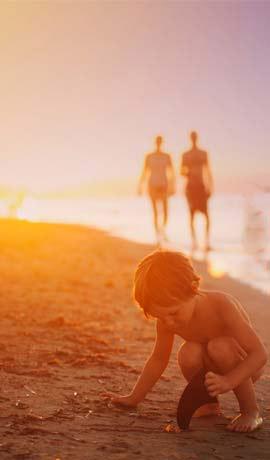 niño jugando en la playa al atardecer