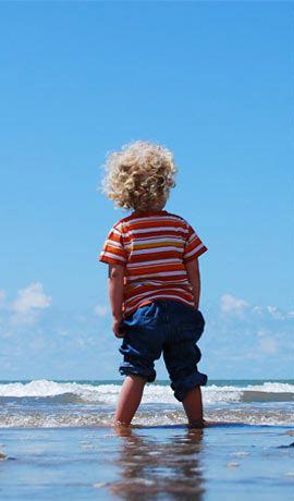 Niño descalzo mojandose los pies en la orilla