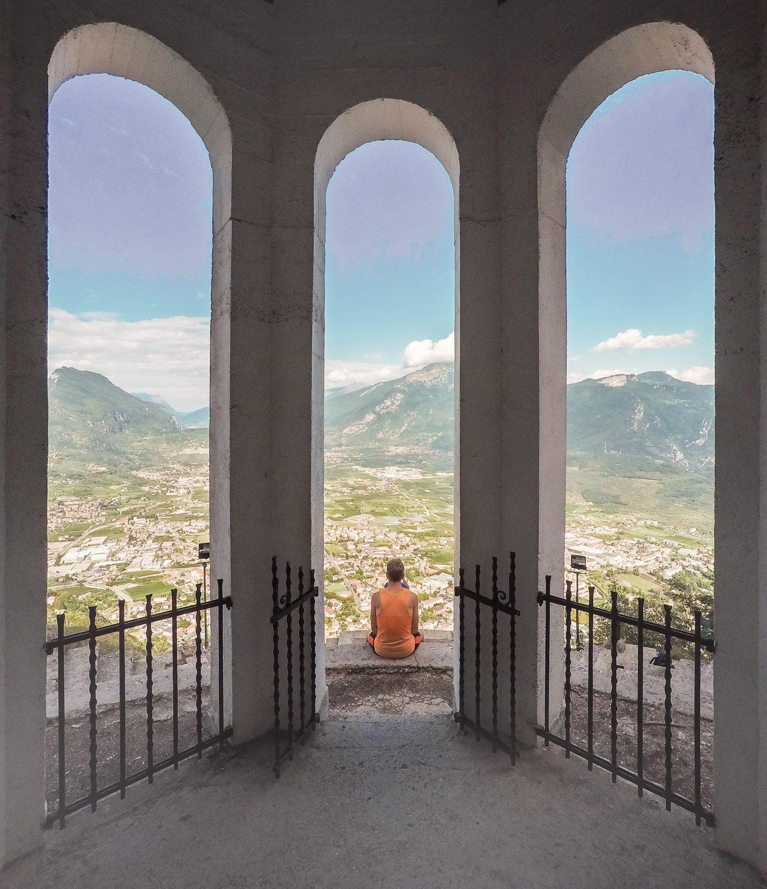 Eine Frau sitzt vor einem Gebäude mit einem Ausblick über Riva del Garda.