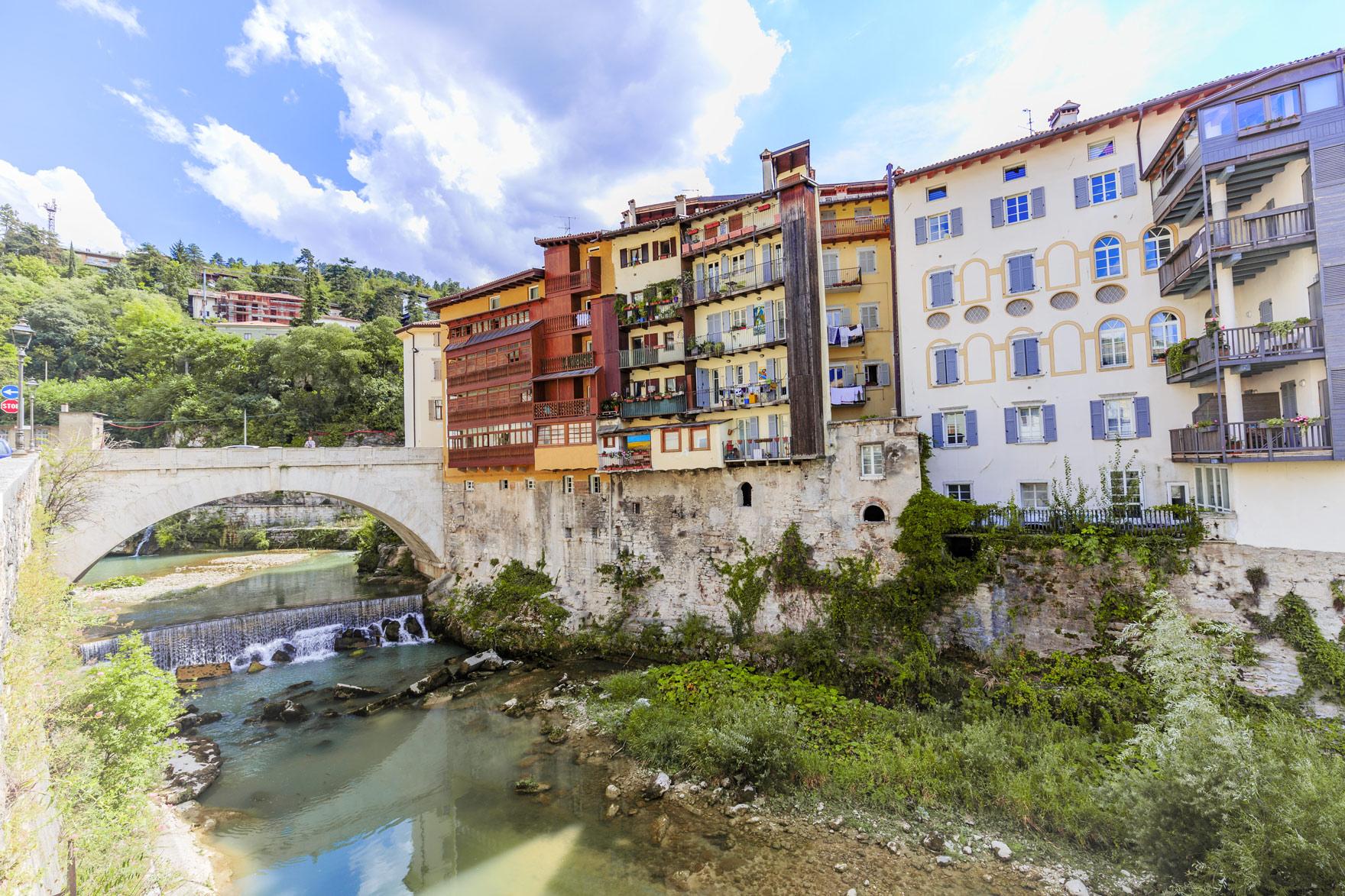 Bunte Häuser an einem Fluss in Rovereto.