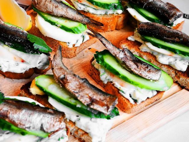 Жареный черный хлеб со шпротами, маслом и огурцом