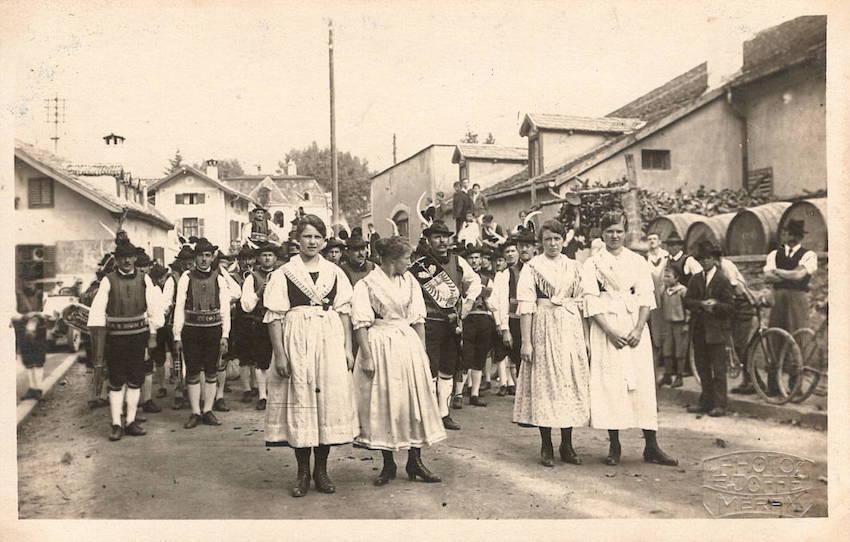 Cartolina fotografica rappresentante una processione di uomini e donne in vestiti popolari.