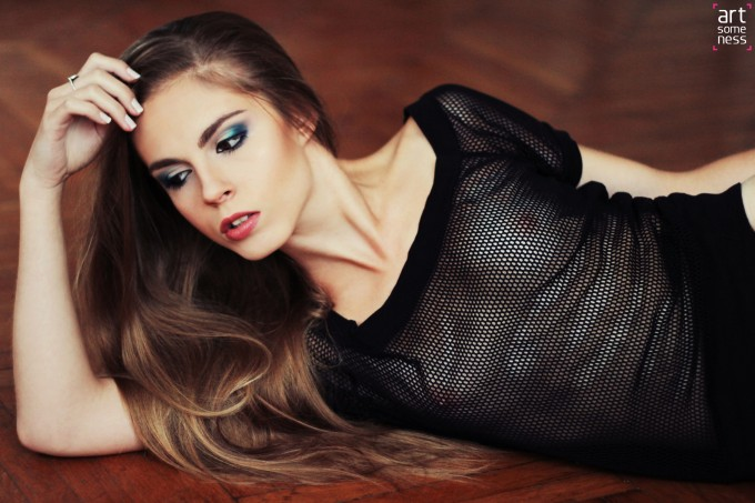 model in mesh shirt and strings laying on wooden floor