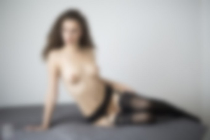 naked model with curly hair in stockings sitting on bed