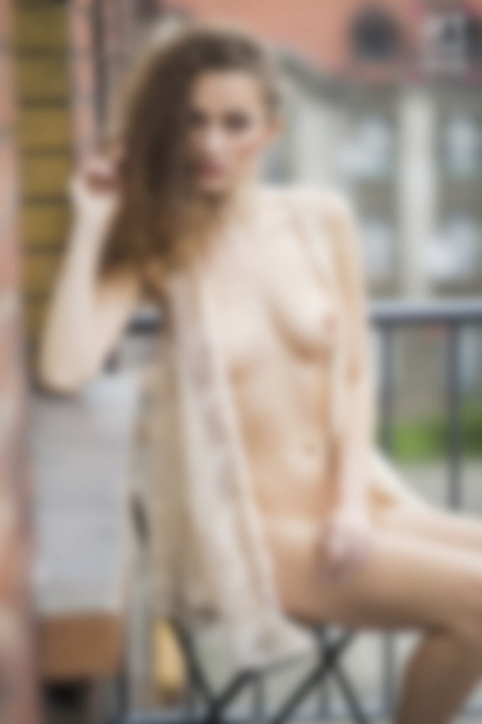 naked model with curly hair and visible breasts sitting on balcony
