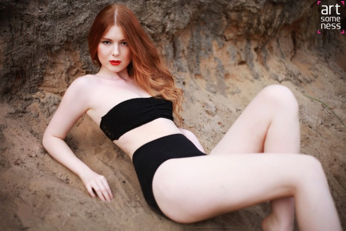 redhead girl laying on a sand in black lingerie