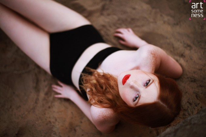 Redhead model laying on sand in lingerie