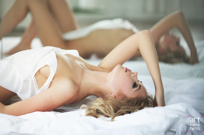 glamour image of blonde model laying naked covered with pyjama in front of mirror