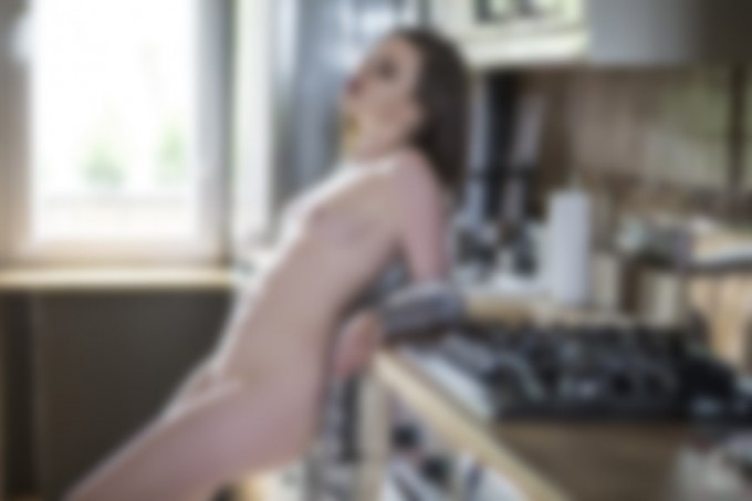 brunette model standing naked in the kitchen