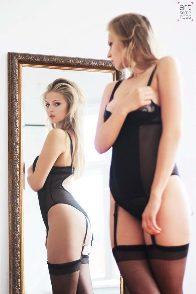 blonde looking at herself in a mirror in black body and stockings
