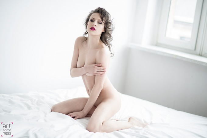 naked girl sitting on bed covering her body with a hands