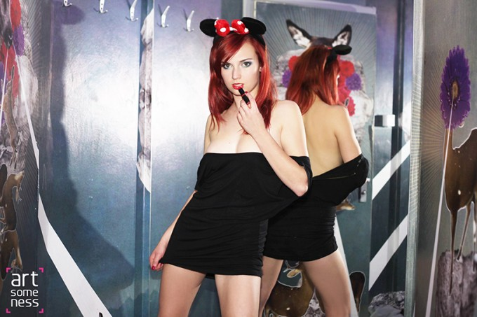 Red haired teenage model standing back to window in black dress and mouse ears and lipstick