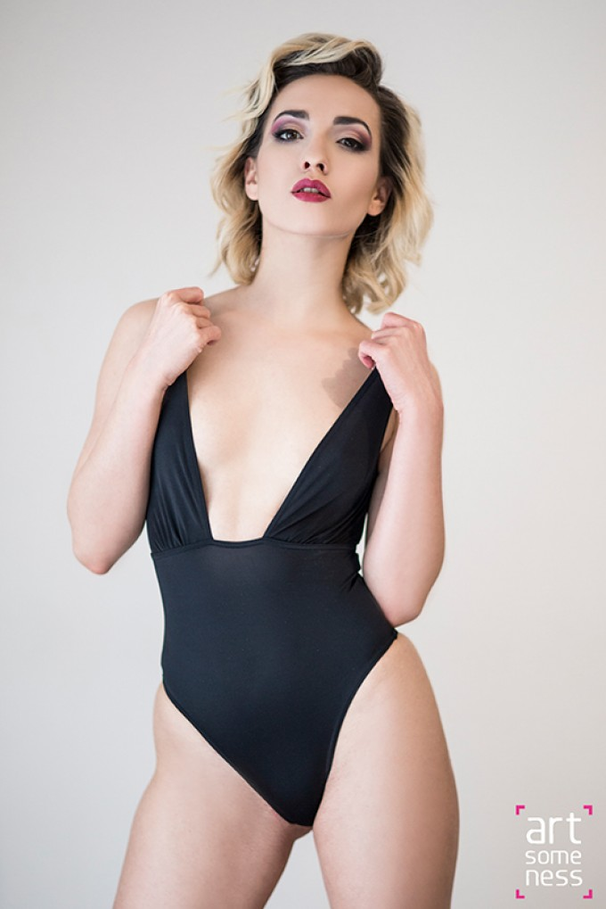 blonde model Alexandra standing in black bodysuit