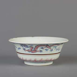 A Chinese blue, white and copper red 'dragon and phoenix' bowl, Kangxi mark, 19th/20th C.