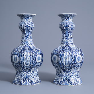 A pair of Dutch Delft blue and white garlic-head mouth vases with floral design, Makkum, 19th C.