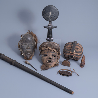Three African wooden masks, votive objects and a cane, 20th C.