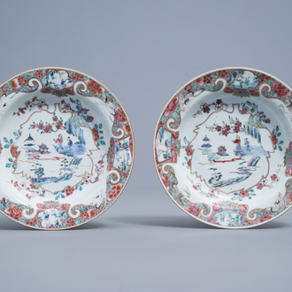 A pair of Chinese famille rose deep plates with figures in a landscape and cranes, Yongzheng/Qianlong