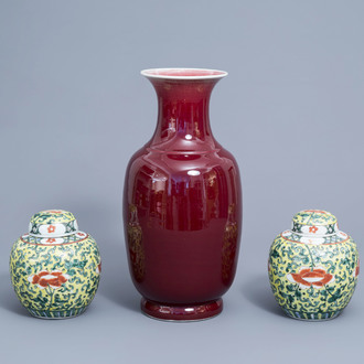 A pair of Chinese famille verte jars and covers with floral design and a monochrome sang de boeuf vase, 19th/20th C.