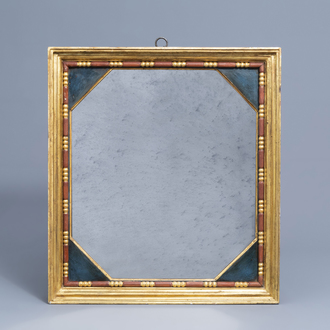 An octagonal mirror in a gilt and polychrome decorated wooden frame, 20th C.