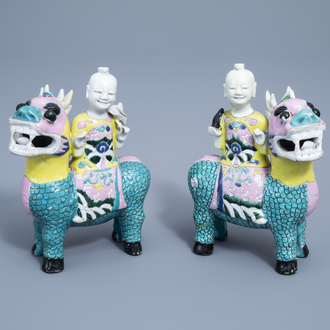 A pair of Chinese famille rose groups of boys seated on qilins, Qianlong/Jiajing