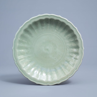 A lotus shaped Chinese Longquan celadon charger with underglaze floral design, Ming