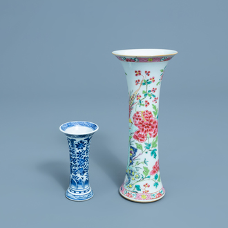 A Chinese famille rose gu vase with a bird among blossoming branches and a blue and white gu vase with floral and relief design, Kangxi/Yongzheng