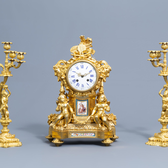 A French gilt bronze Sèvres style mantel clock and a pair of Louis XV style four light candelabra, 19th C.