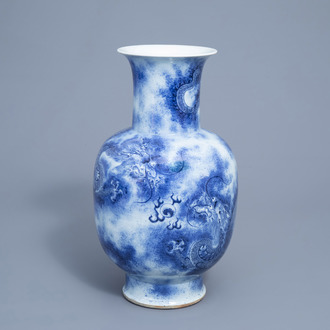 A Chinese blue and white baluster vase with dragons chasing the pearl, 19th C.