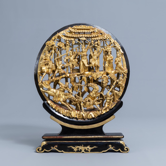A Chinese reticulated gilt wood 'battle scene' medallion on stand, 19th C.