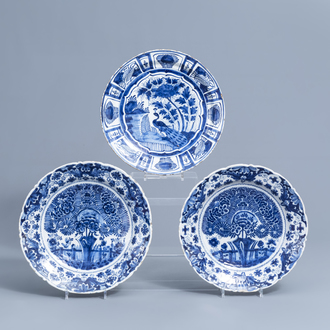 A pair of Dutch Delft blue and white 'tea tree' chargers and one with a peacock, 18th C.