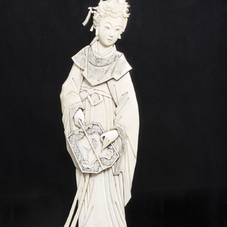 A Chinese ivory carving of a lady with a fan mounted on a plaque, first half of the 20th C.