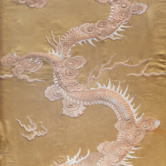 A Chinese vertical silk embroidery with a dragon chasing the pearl, 19th C.