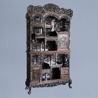 A Chinese reticulated wooden display cabinet with dragons and floral design, 19th C.