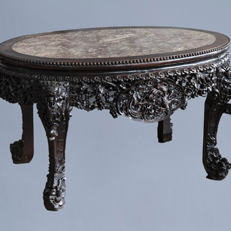 An oval Chinese finely carved wooden table with marble top, 19th C.