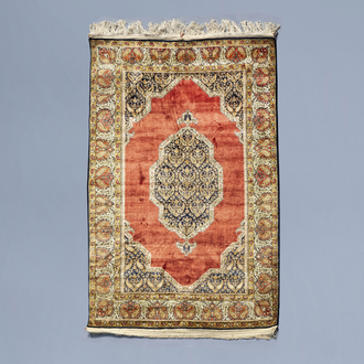 A fine Oriental rug with a central medallion and floral design, silk on cotton, 20th C.