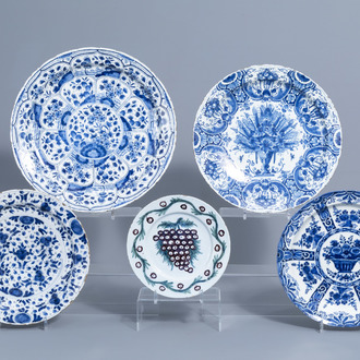 Four Dutch Delft blue and white chargers and a polychrome plate with floral design, 18th C.