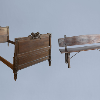 A rustic wooden bench and a Louis XVI style bed with carved floral design, 19th/20th C.