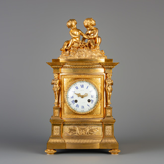 A French gilt bronze mantel clock crowned with two putti and a lizard, 19th C.