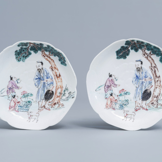 A pair of Chinese famille rose lotus shaped saucers with a scholar and his apprentices, Yongzheng