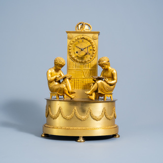 A fine French Empire gilt bronze mantel clock with children reading in a library, 19th C.